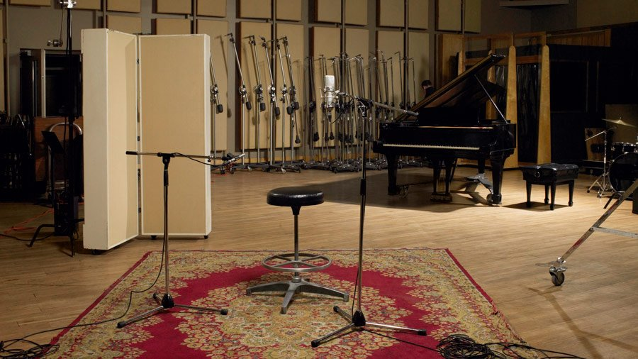 Photo of recording studio set with piano and microphones